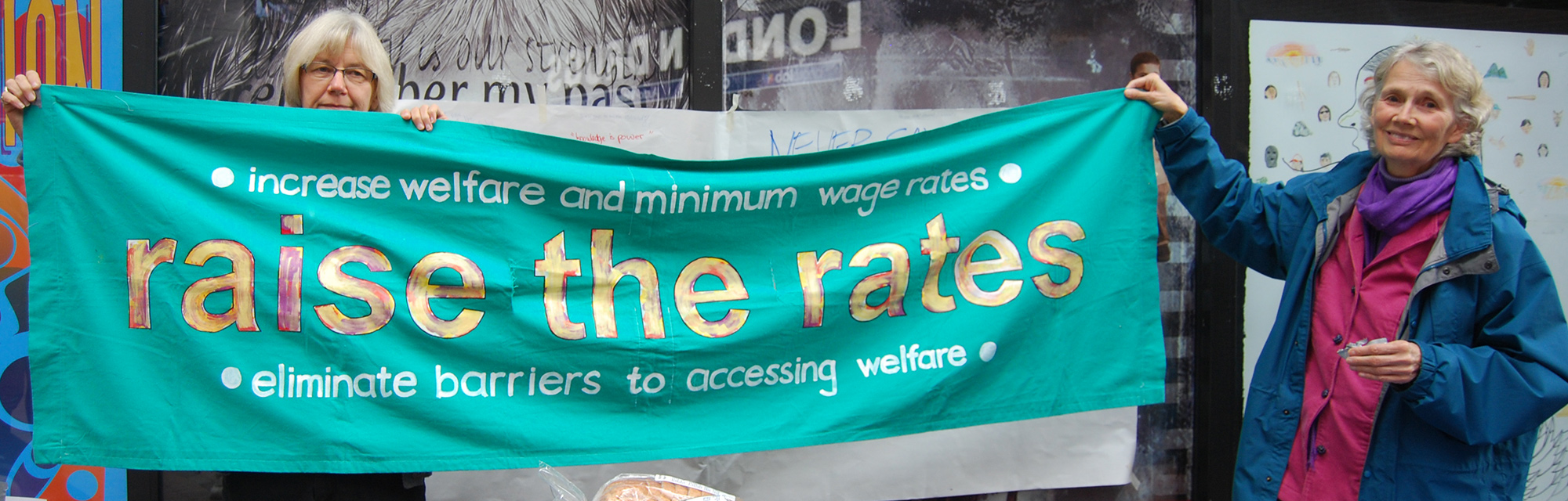 Photo of Jean and Irene holding the Raise the Rates banner at the Oct 16th Welfare Food Challenge Launch